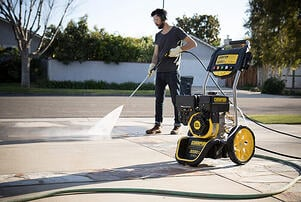 A man using a power washer, one of Plytix customer Champion Power Equipment's products