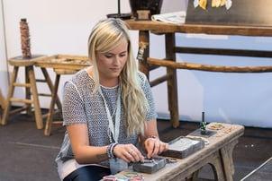 Mai Johansson of Mai Copenhagen, a Plytix customer, setting up a display of her jewelry
