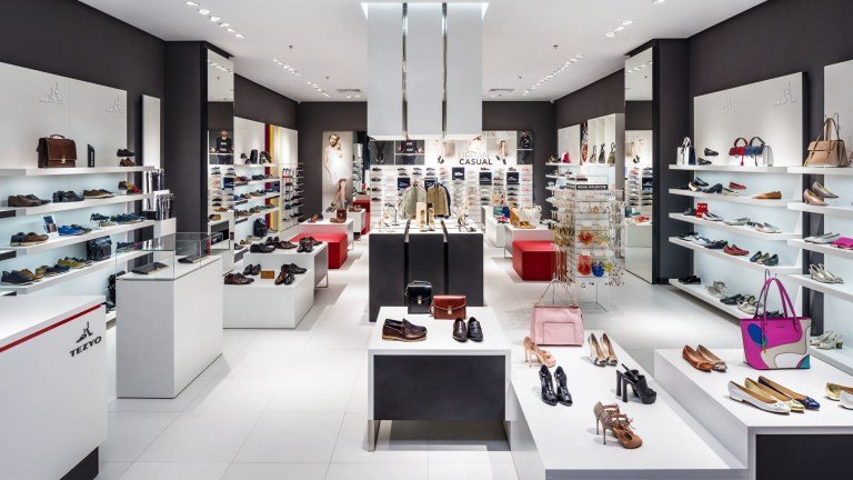 In-store display of one of Otter's physical stores - white, sleek with modern shelves and shoes